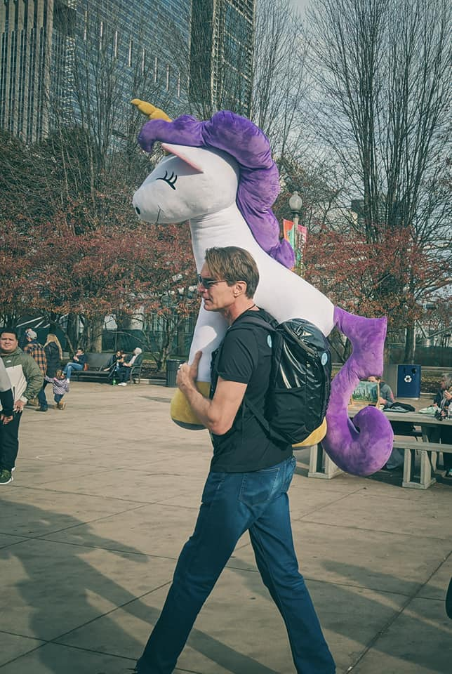 giant unicorn plush in chicago with tall man